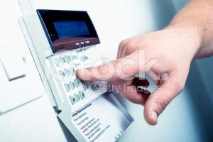 person inputting a code into a security system
